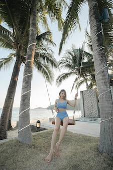 Glückliche frau im blauen bikini, schwingen an kokospalme am strand