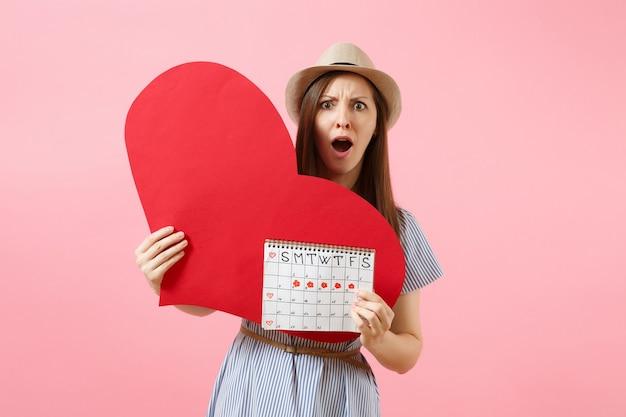 Glückliche frau im blauen kleidsommerhut, der leeres leeres großes rotes herz, kalender der weiblichen perioden hält und menstruationstage einzeln auf hintergrund überprüft. gynäkologisches konzept des medizinischen gesundheitswesens. platz kopieren