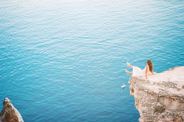 Glückliche frau im freien am rande der klippenküste genießen die aussicht auf berggipfelfelsen