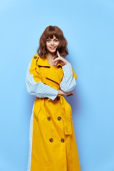Glückliche frau im gelb gestreiften mantel