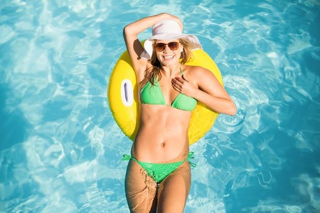 Glückliche frau im grünen bikini, der auf aufblasbares rohr im swimmingpool schwimmt
