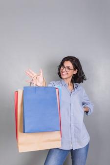 Glückliche frau im hemd, das einkaufstaschen zeigt