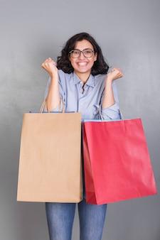 Glückliche frau im hemd mit einkaufstaschen