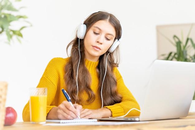 Glückliche frau im kabellosen kopfhörer, die online-kurs studiert, pc verwendet und im notizblock schreibt