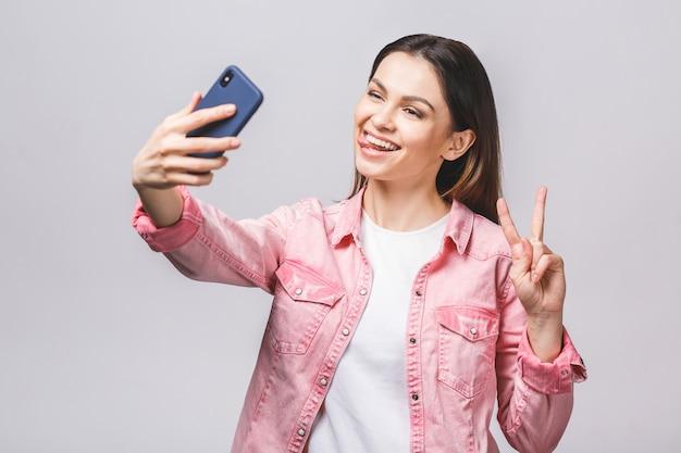 Glückliche frau im lässigen mit strahlendem lächeln, das selfie macht und v-zeichen zeigt, lokalisiert gegen weißen hintergrund.