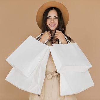 Glückliche frau im mantel mit vielen einkaufsnetzen