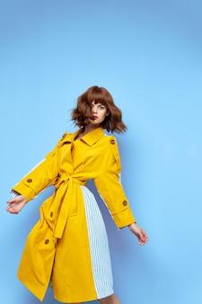 Glückliche frau im modischen gelben mantel mit gürtel und runden knöpfen