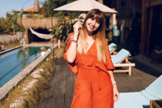 Glückliche frau im orangefarbenen kleid, das im tropischen authentischen resort während der ferien aufwirft