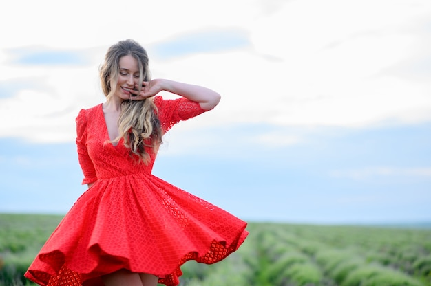 Glückliche frau im roten kleid, die im lavendelfeld tanzt und springt