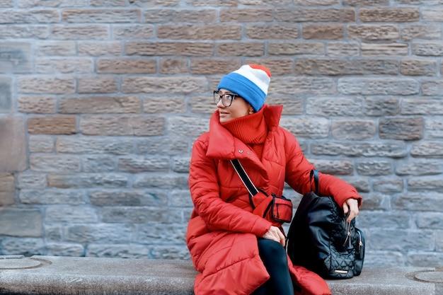 Glückliche frau im roten mantel, hut, der bei kaltem wetter durch stadt geht