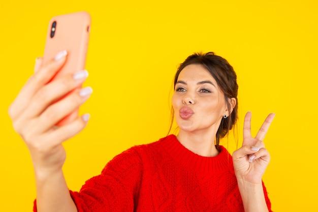 Glückliche frau im roten pullover mit telefon, das foto und küsse vor der kamera macht.