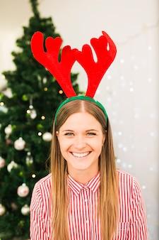 Glückliche frau im rotwildgeweihstirnband nahe weihnachtsbaum