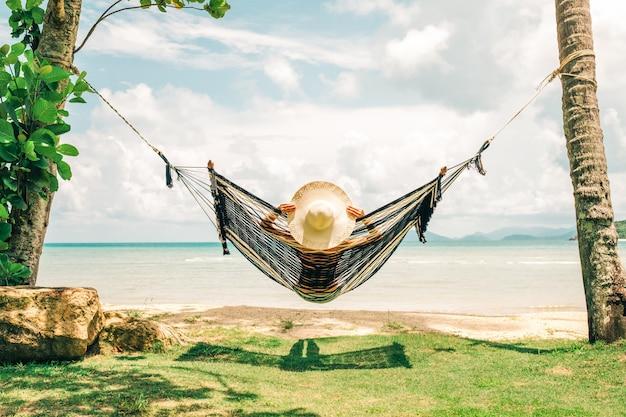 Glückliche frau im schwarzen bikini, der in der hängematte entspannt