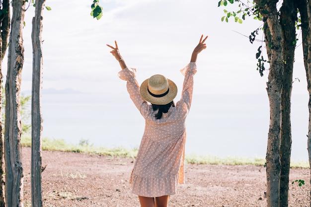 Glückliche frau im sommer süßes kleid und strohhut im urlaub mit tropischen exotischen ansichten