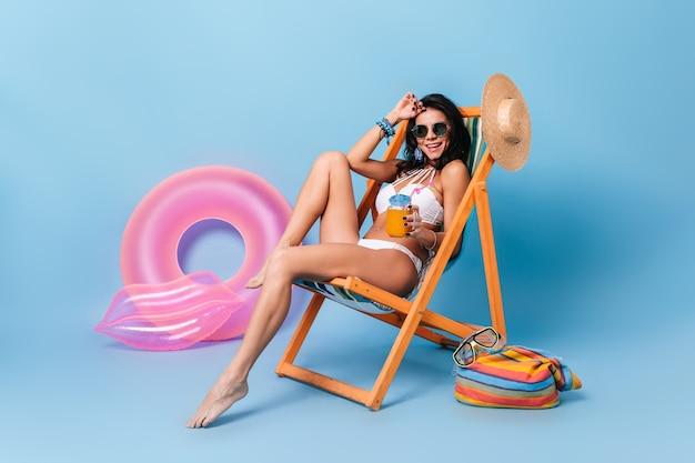 Glückliche frau im sonnenbrillen- und badeanzug, der orangensaft trinkt