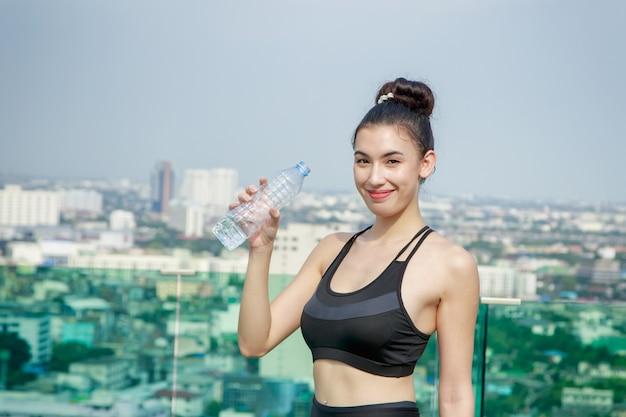 Glückliche frau im sport kleidet trinkwasser nach training am stadt scape