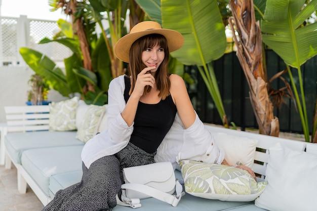 Glückliche frau im strohhut, der zu hause auf luxusterrasse kühlt, posierend nahe tropischem garten.