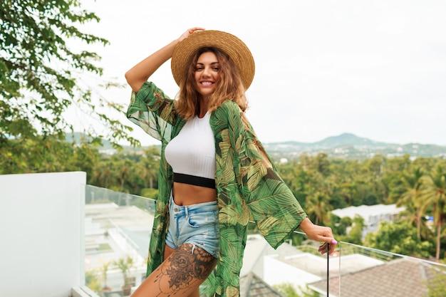 Glückliche frau im strohhut und in den sexy shorts der jeans mit tätowierung, die auf terrasse steht