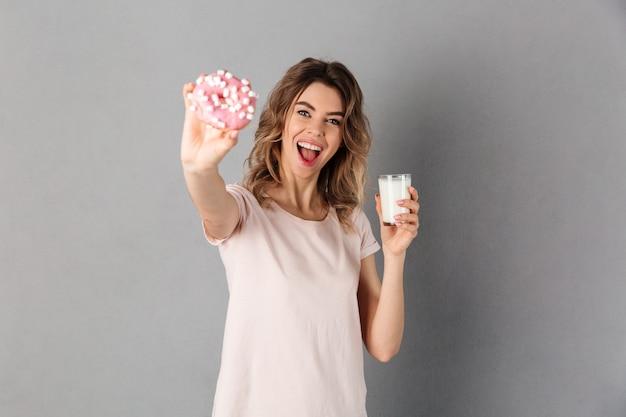 Glückliche frau im t-shirt, das tasse milch hält, während donut zeigt. konzentrieren sie sich auf spenden