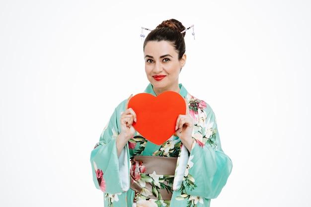 Glückliche frau im traditionellen japanischen kimono, der ein herz aus pappe zeigt, das fröhlich auf weiß lächelt