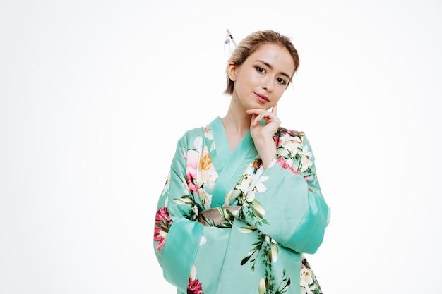 Glückliche frau im traditionellen japanischen kimono mit nachdenklichem ausdruck mit der hand am kinn, die auf weiß denkt