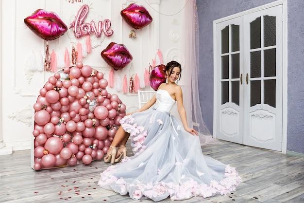 Glückliche frau im tüllkleid mit rosa ballons. luxus