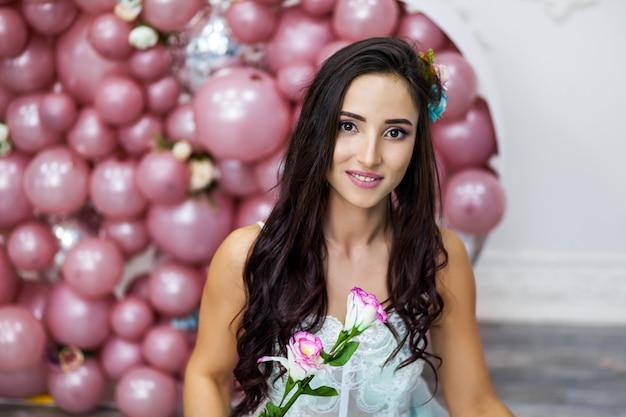 Glückliche frau im tüllkleid mit rosa ballons.