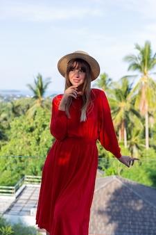 Glückliche frau im urlaub im roten sommerkleid und im strohhut auf balkon mit tropischem blick auf meer und plam-bäume.