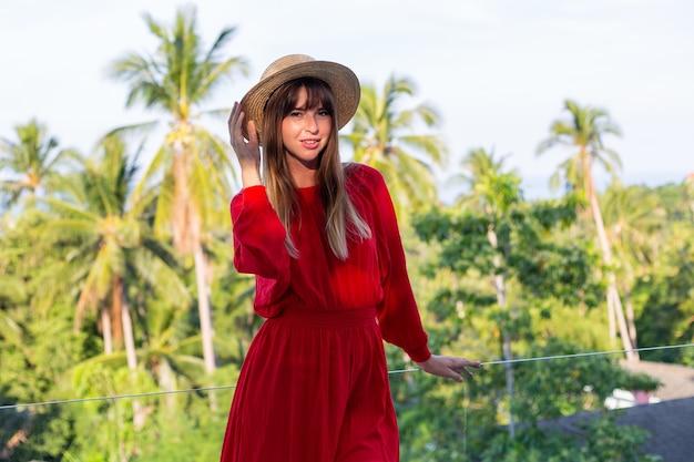 Glückliche frau im urlaub im roten sommerkleid und im strohhut auf balkon mit tropischem blick auf meer und plam-bäume. Kostenlose Fotos