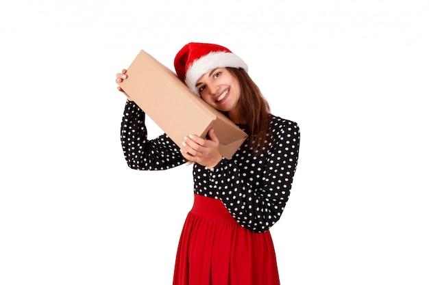 Glückliche frau im weihnachtshut umarmt ein geschenk, das im recyclingpapier eingewickelt wird. isoliert