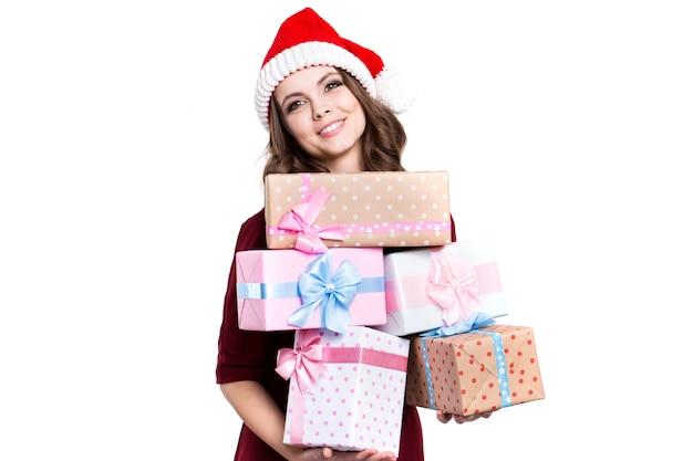 Glückliche frau im weihnachtsmannhut mit geschenken lokalisiert