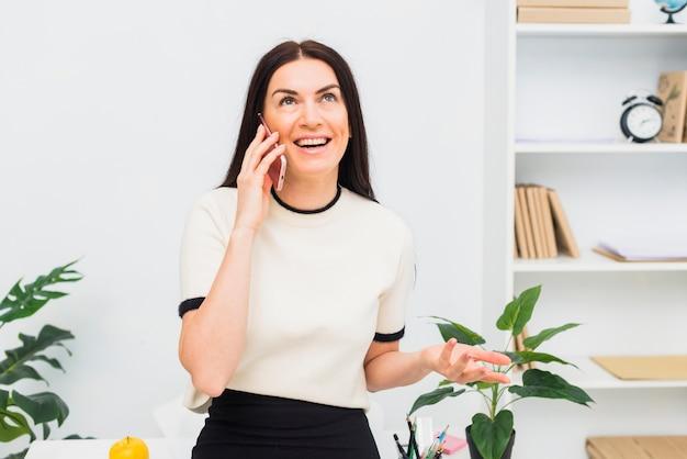 Glückliche frau im weiß telefonisch sprechen im büro