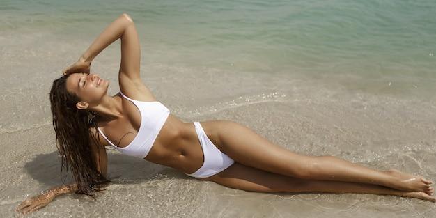 Glückliche frau im weißen badeanzug, der auf einem strand im wasser mit geschlossenen augen am meer liegt. lächelnd