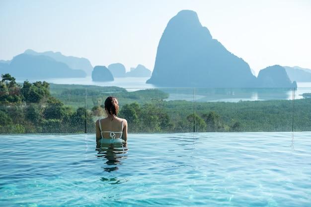 Glückliche frau im weißen badeanzug, der im luxuspoolhotel gegen phang nga buchthintergrund schwimmt