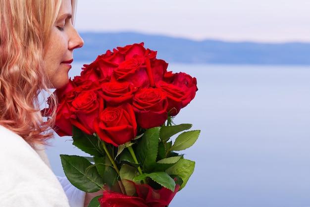 Glückliche frau im weißen gewand mit einem strauß roter rosen schaut vom hotelbalkon auf das meer