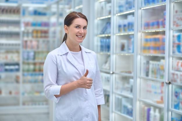 Glückliche frau im weißen kittel in der apotheke