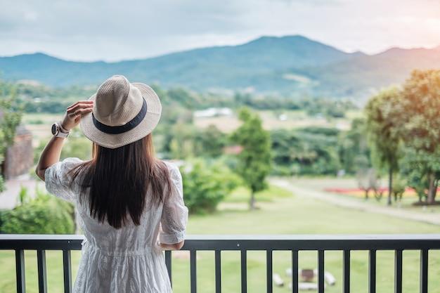 Glückliche frau im weißen kleid und im hut, die schöne naturansicht suchen.