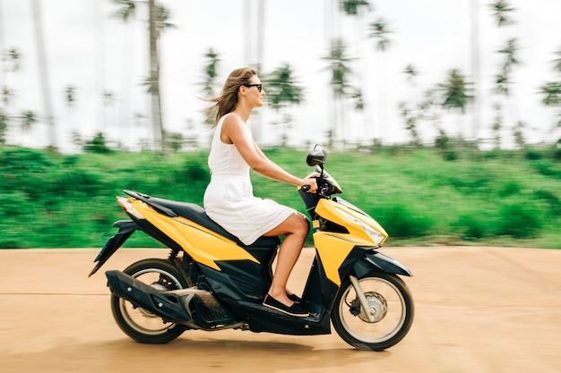 Glückliche frau im weißen kleid und in der sonnenbrille, die motorrad reitet
