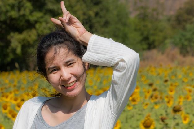 Glückliche frau in den feldsonnenblumen am sonnigen tag
