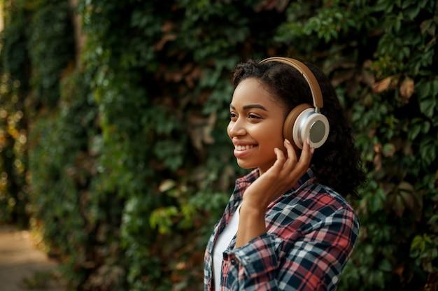 Glückliche frau in den kopfhörern, die musik im sommerpark hören. weiblicher musikfan, der draußen geht, mädchen in den kopfhörern, draußen