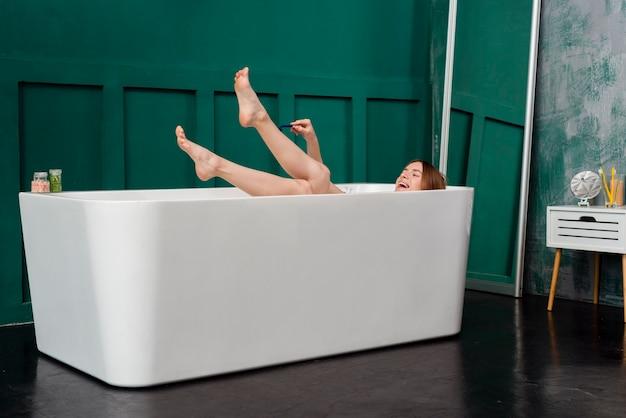Glückliche frau in der badewanne, die ihre beine rasiert