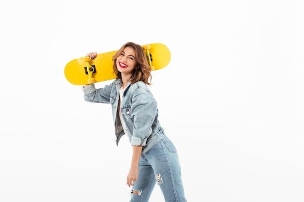 Glückliche frau in der denimkleidung, die mit skateboard über weißer wand aufwirft
