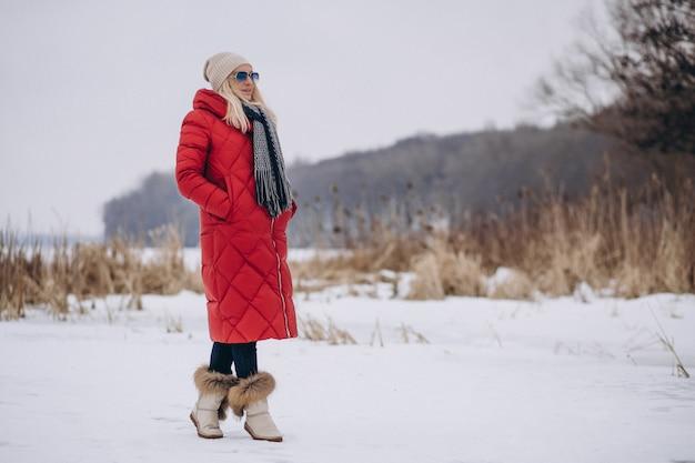 Glückliche frau in der roten jacke draußen im winter