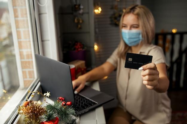 Glückliche frau in der schutzmaske, die bankkarte in der hand nimmt und online-shopping zu hause macht, um weihnachtsgeschenk während quarantäne zu kaufen. konzentriert auf karte.