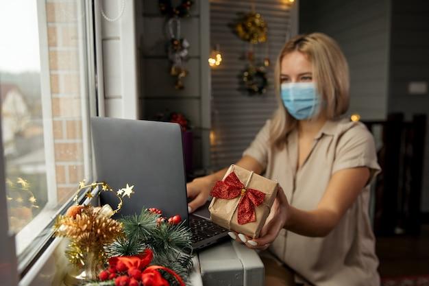 Glückliche frau in der schutzmaske, die geschenk in der hand nimmt und online-shopping zu hause macht, um weihnachtsgeschenk während der quarantäne zu kaufen. konzentriert sich auf geschenk.