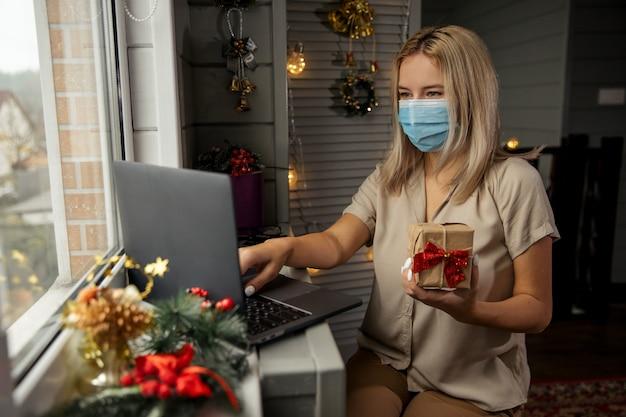 Glückliche frau in der schutzmaske, die geschenk in der hand nimmt und online-shopping zu hause macht, um weihnachtsgeschenk während der quarantäne zu kaufen.