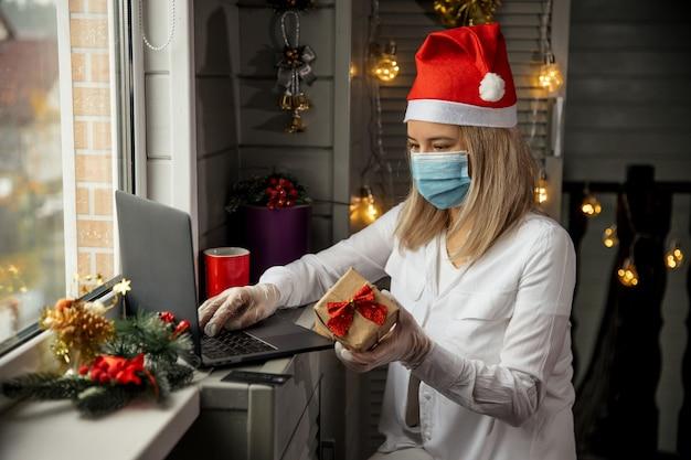 Glückliche frau in der schutzmaske, in den handschuhen und im roten hut, die geschenk in der hand nehmen und online-shopping zu hause tun, um weihnachtsgeschenk während der quarantäne zu kaufen.