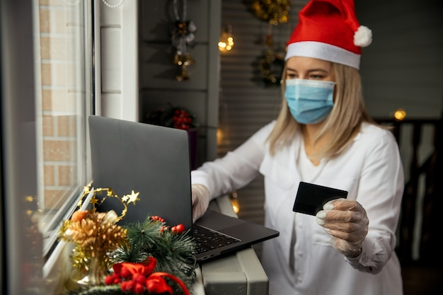 Glückliche frau in der schutzmaske, in den handschuhen und im roten hut, die kreditkarte in hand nehmen und online-shopping zu hause tun, um weihnachtsgeschenk während der quarantäne zu kaufen.