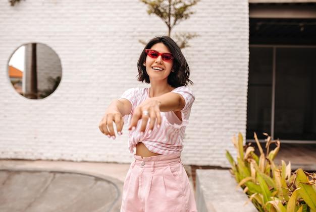 Glückliche frau in der sonnenbrille, die auf straße mit ausgestreckten händen aufwirft. außenaufnahme der gebräunten frau im rosa t-shirt.