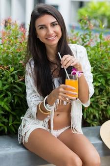 Glückliche frau in der stilvollen weißen strandkleidung boho, die nahe tropischem pool im luxushotel sitzt und orange cocktail oder saft genießt.